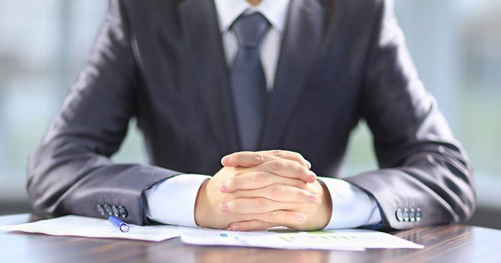 empresário sentado em uma mesa e pensando sobre os riscos contábeis