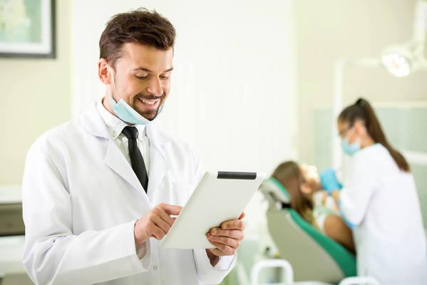 Profissional que conseguiu emitir CNPJ para dentista mexendo em um tablet