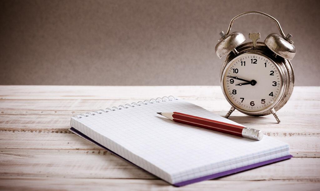 Agenda, papel e relógio indicando planejamento para ter controle financeiro para superar a crise