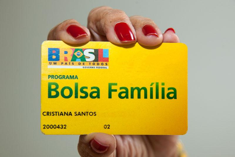 Pessoa segurando cartão do Bolsa Família, programa que foi afetado pelas Medidas do Governo Federal em relação ao Coronavírus