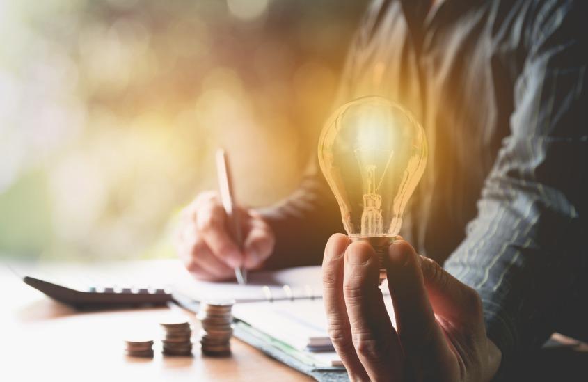 Empreendedor segurando uma lâmpada acesa, representando uma ideia