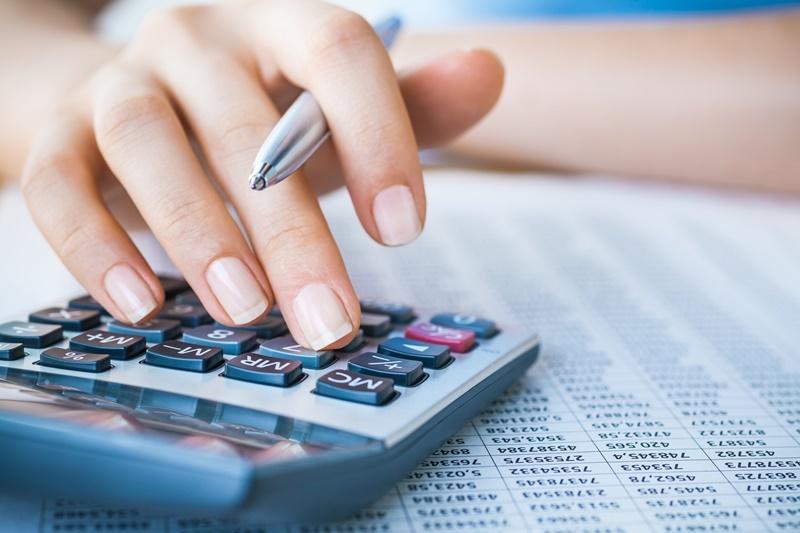 Empresário usando uma calculadora para conseguir realizar redução de impostos