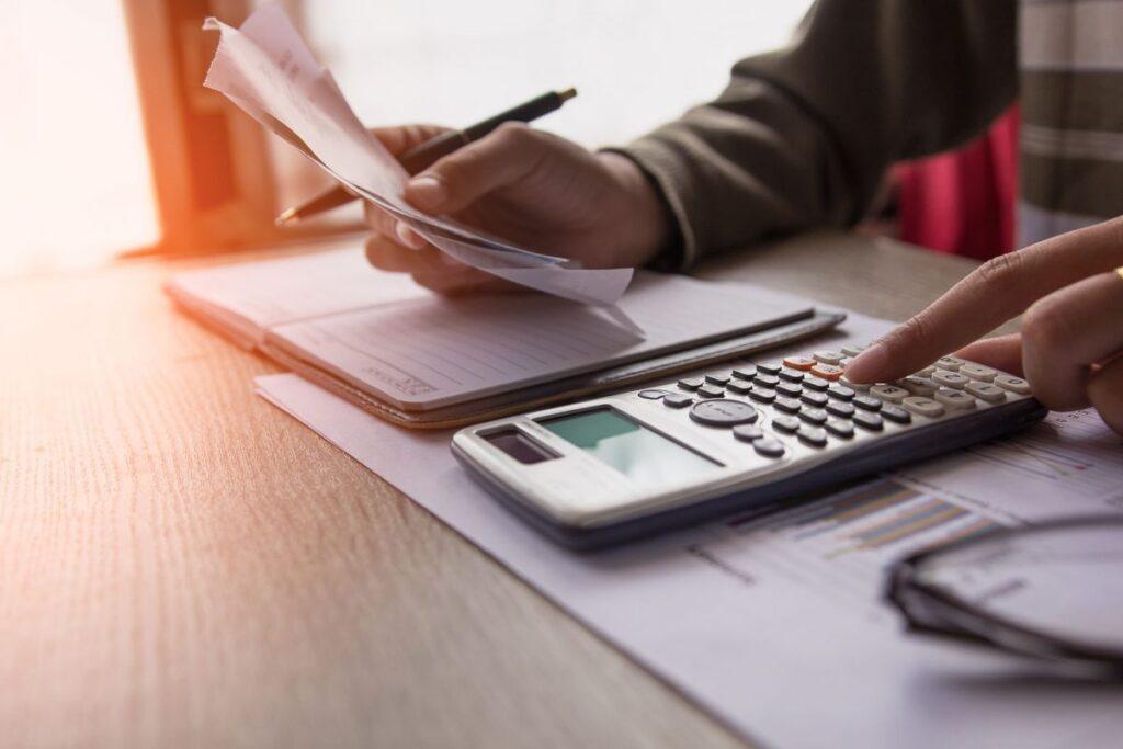 Empreendedor realizando cálculos para saber se deve ou não contratar uma plataforma para contadores