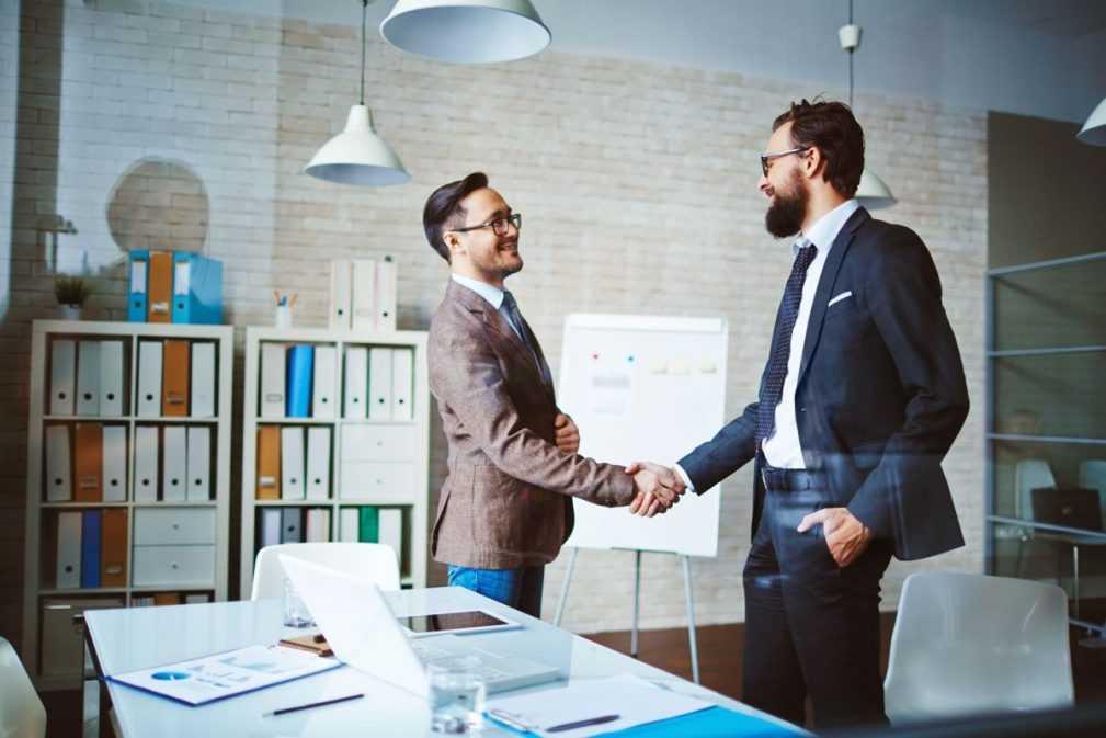 Dois homens usando terno apertando as mãos depois de encontrarem uma contabilidade para franquias